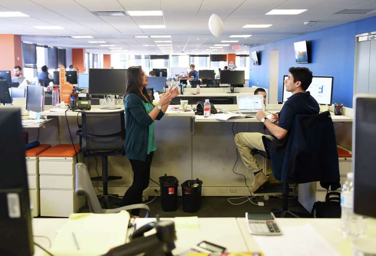 Indeed Senior Account Executive Kanwal Pervaz and Account Executive Dan Zaleski toss a football while working at the Indeed Stamford Headquarters in Stamford, Conn. Thursday, Feb. 18, 2016. The employment-related search engine for job listings is undertaking its second major expansion in Stamford in as many years at its 177 Broad Street offices.