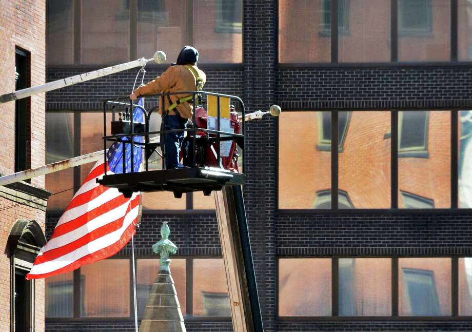 Joe Boemio of Saxton Sign of Castleton restrings an American flag that became tangled at the Bank of America building at State and Pearl Streets Friday, Feb. 26, 2016, in Albany, N.Y.  (John Carl D'Annibale / Times Union) Photo: John Carl D'Annibale