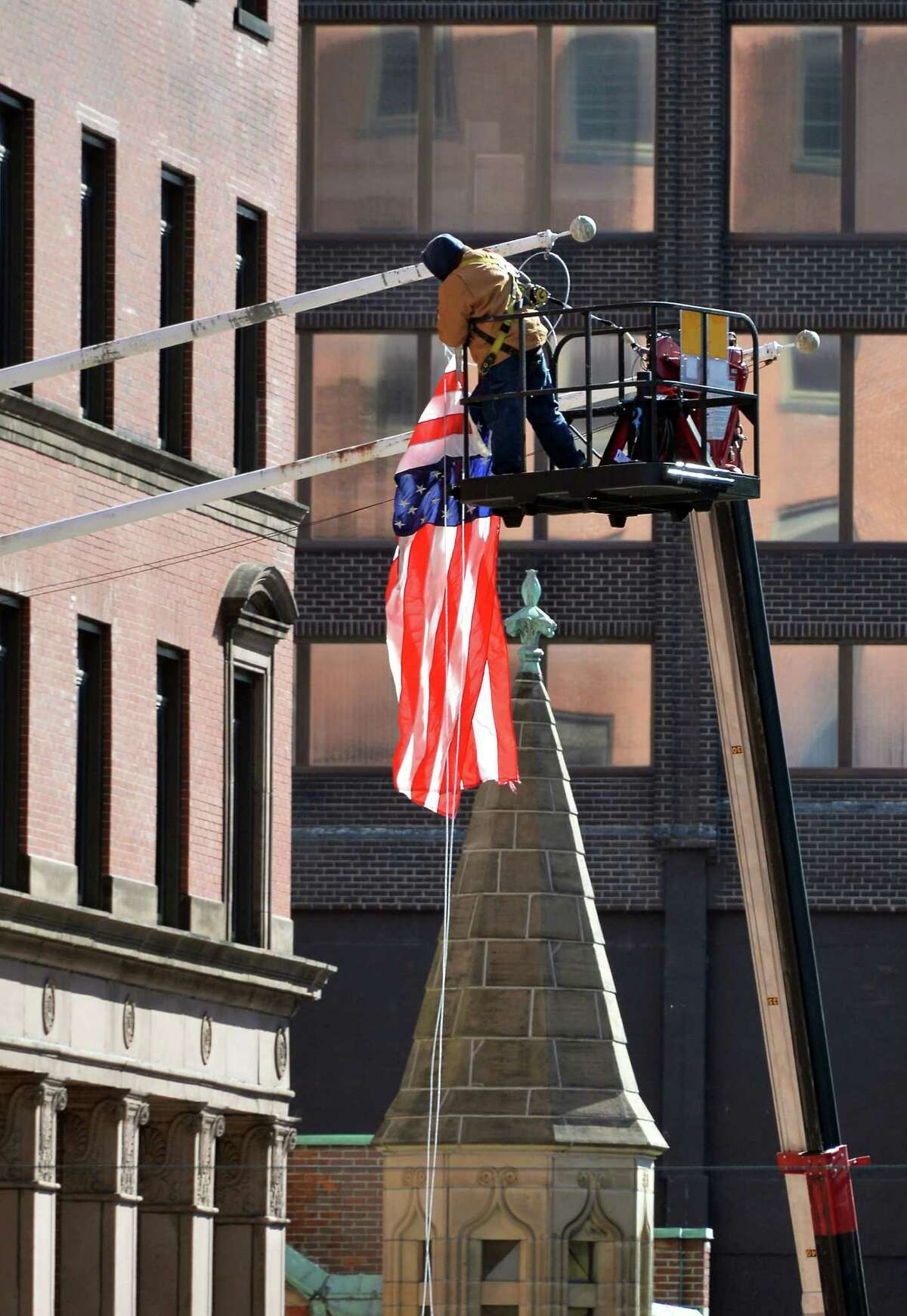 Joe Boemio of Saxton Sign of Castleton restrings an American flag that became tangled at the Bank of America building at State and Pearl Streets Friday, Feb. 26, 2016, in Albany, N.Y. (John Carl D'Annibale / Times Union)