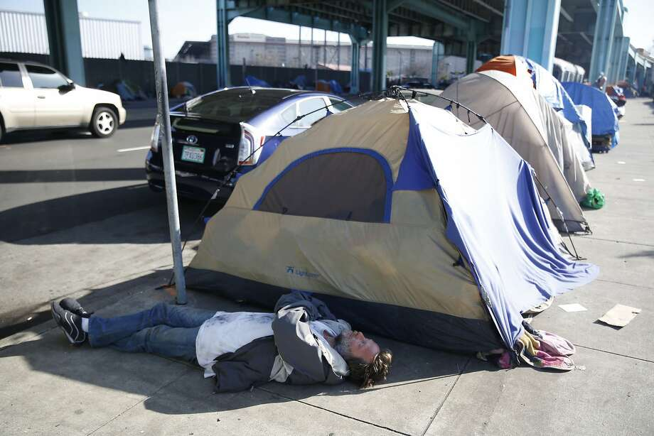 A man lies on the ground in the shade cast by the shadow of a tent along 13th Street on Thursday, February 25, 2016 in San Francisco, California. Photo: Lea Suzuki, The Chronicle