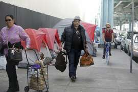 Papa Smirf (center) carries some of his belongings down the 13th Street as he prepares to move from his tent on 13th Street to Pier 80 with help from the San Francisco Homeless Outreach Team on Thursday, February 25, 2016 in San Francisco, California.