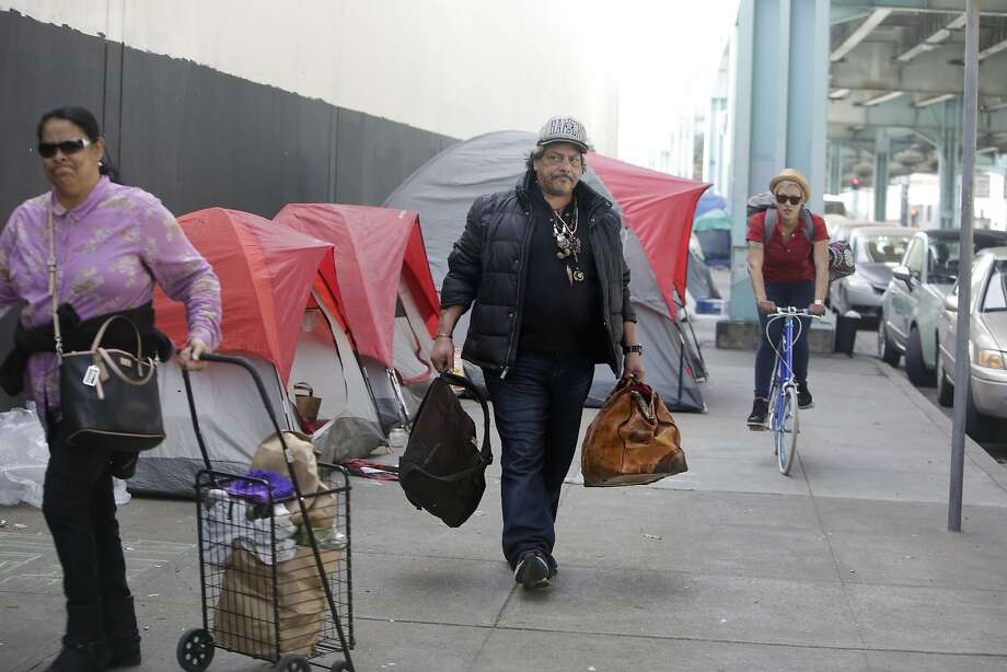 Papa Smirf (center) carries some of his belongings down the 13th Street as he prepares to move from his tent on 13th Street to Pier 80 with help from the San Francisco Homeless Outreach Team on Thursday, February 25, 2016 in San Francisco, California. Photo: Lea Suzuki, The Chronicle