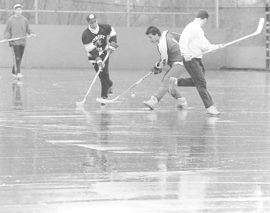 Local youths play pick-up street hockey in Scalzi Park on Jan. 6, 1991, undeterred by the rain and slush. Photo: Tom Ryan / Tom Ryan / Stamford Advocate