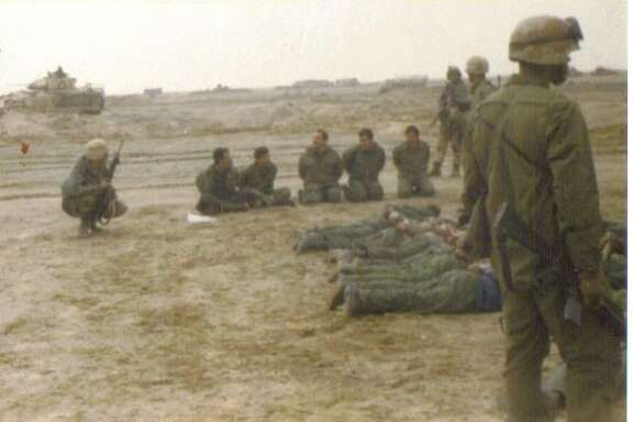 """Mike Glenn (far left) in the Gulf War: """"As the tankers in my cav troop continued their fight, I led my infantry mortar soldiers & artillery forward observers on a mission to clear a series of bunkers at an airstrip near the Rumaila oil field in the Euphrates Valley of southern Iraq. I'm on the left, crouching with the rifle. I let the Iraqi enlisted soldiers sit up but told the officers to get on their stomachs. (They were assholes.)"""""""