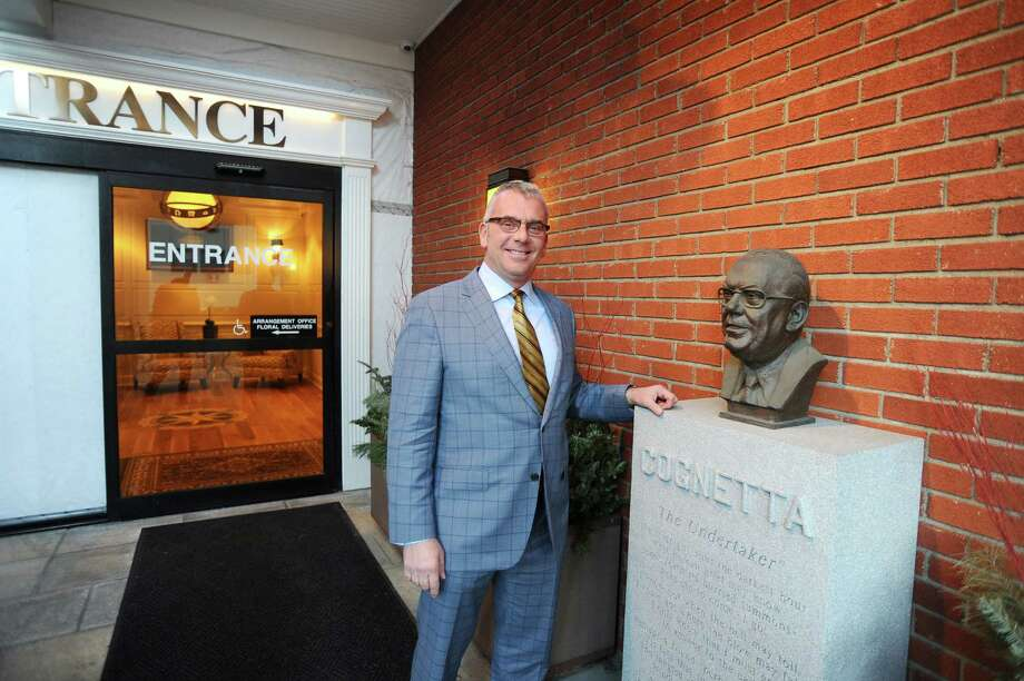 Cognetta Funeral Home owner Nick Cognetta Jr. stands next to a bust of his late father, funeral home founder Nicholas Cognetta, outside the main entrance to the business. Photo: Michael Cummo / Hearst Connecticut Media / Stamford Advocate