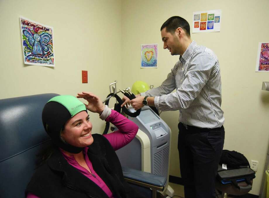 Hakan Hümmet, a clinical support manager for Dignitana, a Swedish company that is manufacturing a product called DigniCap, which allows women undergoing chemotherapy for breast cancer to keep their hair, begins the warmup process for the device, which is worn by Adrianne Frost at the Cancer Therapy and Research Center Friday. Frost is the first person in America, other than in clinical trials, to use the device. Photo: Billy Calzada /San Antonio Express-News / San Antonio Express-News