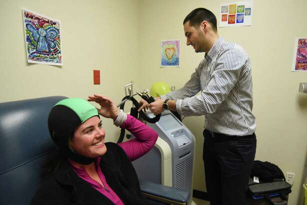 Hakan Hümmet, a clinical support manager for Dignitana, a Swedish company that is manufacturing a product called DigniCap, which allows women undergoing chemotherapy for breast cancer to keep their hair, begins the warmup process for the device, which is worn by Adrianne Frost at the Cancer Therapy and Research Center Friday. Frost is the first person in America, other than in clinical trials, to use the device.