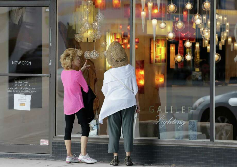 In this Wednesday, Feb. 3, 2016, photo, shoppers stop to look in the window of a lighting store in the Design District of Miami Beach, Fla. On Friday, Feb. 26, 2016, the Commerce Department issues the second of three estimates of how the U.S. economy performed in the October-December quarter. (AP Photo/Lynne Sladky) ORG XMIT: NYBZ502 Photo: Lynne Sladky / AP