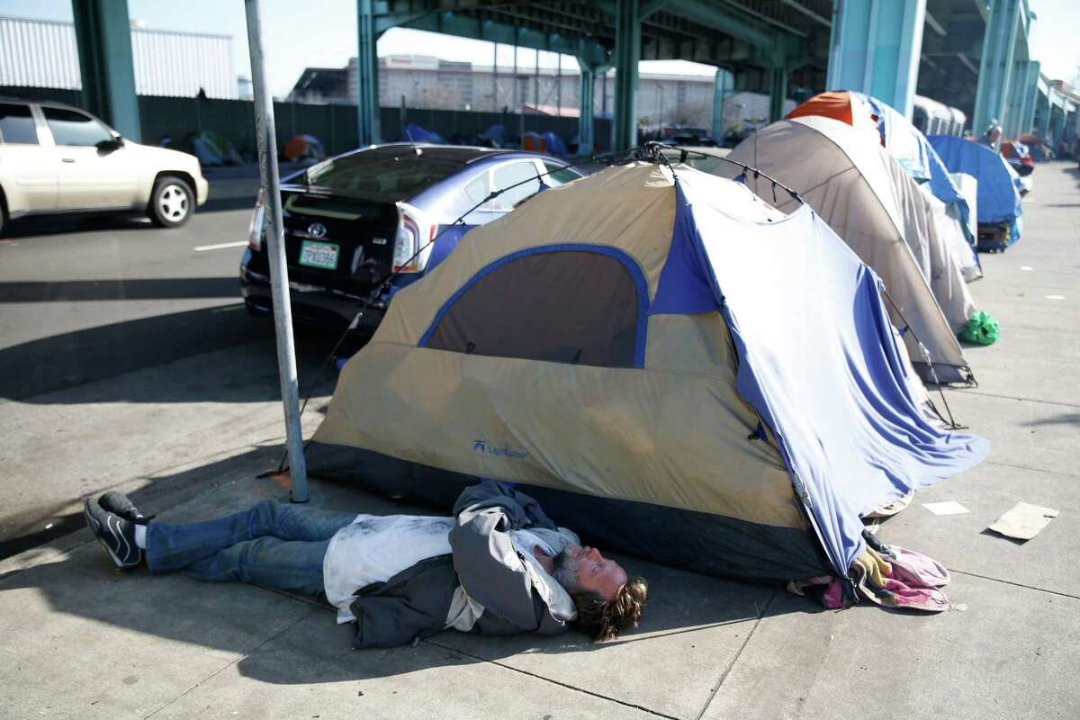 A man lies on the ground in the shade cast by the shadow of a tent along 13th Street on Thursday, February 25, 2016 in San Francisco, California.