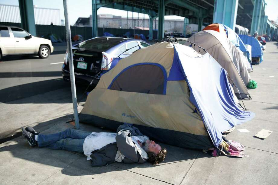 A man lies on the ground in the shade cast by the shadow of a tent along 13th Street on Thursday, February 25, 2016 in San Francisco, California. Photo: Lea Suzuki / The Chronicle / ONLINE_YES