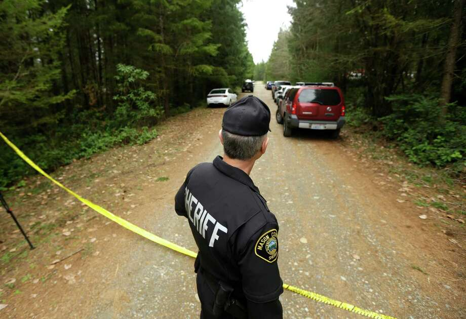 Mason County Sheriff's Chief Criminal Deputy Russ Osterhout looks down a road near a home where a man shot and killed his family, and then himself. A 12-year-old girl survived.  Photo: Ted S. Warren, STF