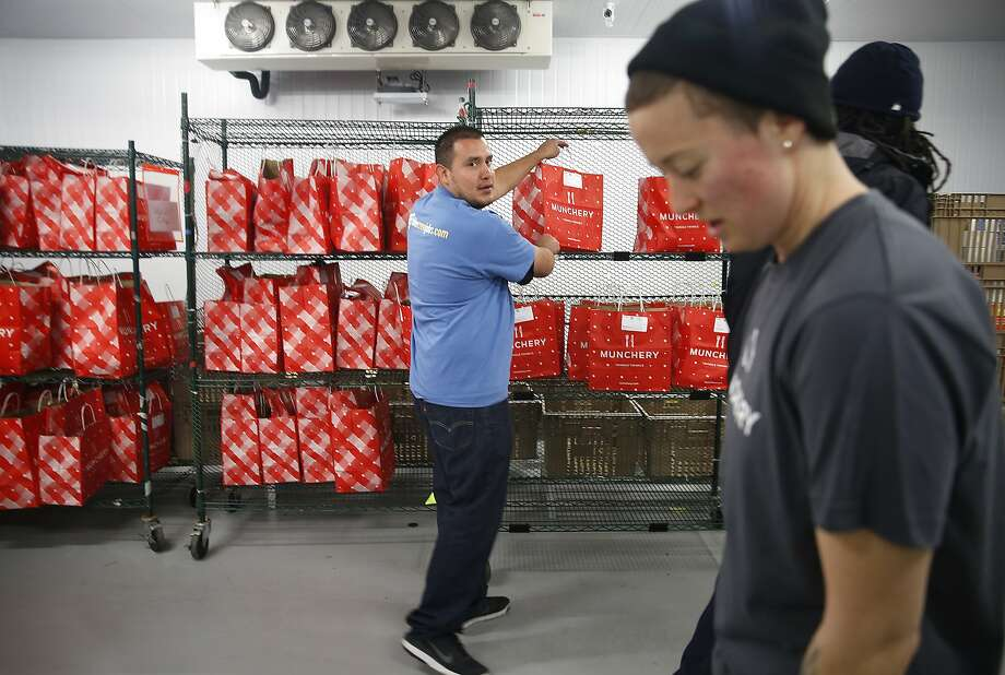 Manuel Valenzuela (middle) helps fill food orders with OPS lead Sammi Roush (right) at the Munchery in San Francisco, California, on friday,  february 26, 2016.  Manuel works for Blue Crew, an on-demand staffing agency for blue collar jobs. Photo: Liz Hafalia, The Chronicle