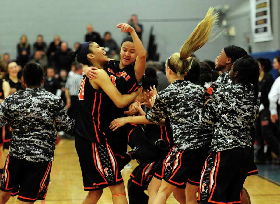 Camille Martinez, center, celebrates with her Stamford teammates after beating Warde 56-48 in Friday's FCIAC girls basketball championship at Ludlowe in Fairfield. Photo: Christian Abraham / Hearst Connecticut Media / Connecticut Post