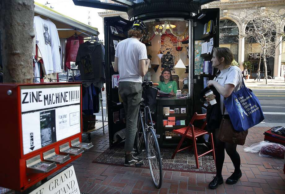 Zine assistant Mae Powell (in newsstand) talks with zine teacher Raphael Villet (left w/bike) as Danielle Truppi (right) delivers new issues of SF State graduate literature in San Francisco, California, on Thursday, February 25, 2016.  The newsstand on Market St., closest to the ferry building, is now called The Grand Newsstand sells zines and independent publications . Photo: Liz Hafalia, San Francisco Chronicle