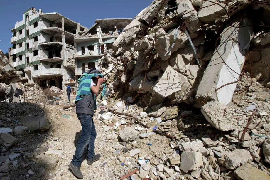"""A Syrian covers his face as he walks with a friend between destroyed buildings in the old city of Homs, Syria, Friday, Feb. 26, 2016. The U.N. Security Council is expected to vote Friday afternoon on a draft resolution endorsing the """"cessation of hostilities"""" in Syria that is set to start at midnight local time. The draft, obtained by The Associated Press, also urges the U.N. secretary-general to resume Syria peace talks """"as soon as possible."""" (AP Photo/Hassan Ammar) ORG XMIT: HAS103 Photo: Hassan Ammar / AP"""