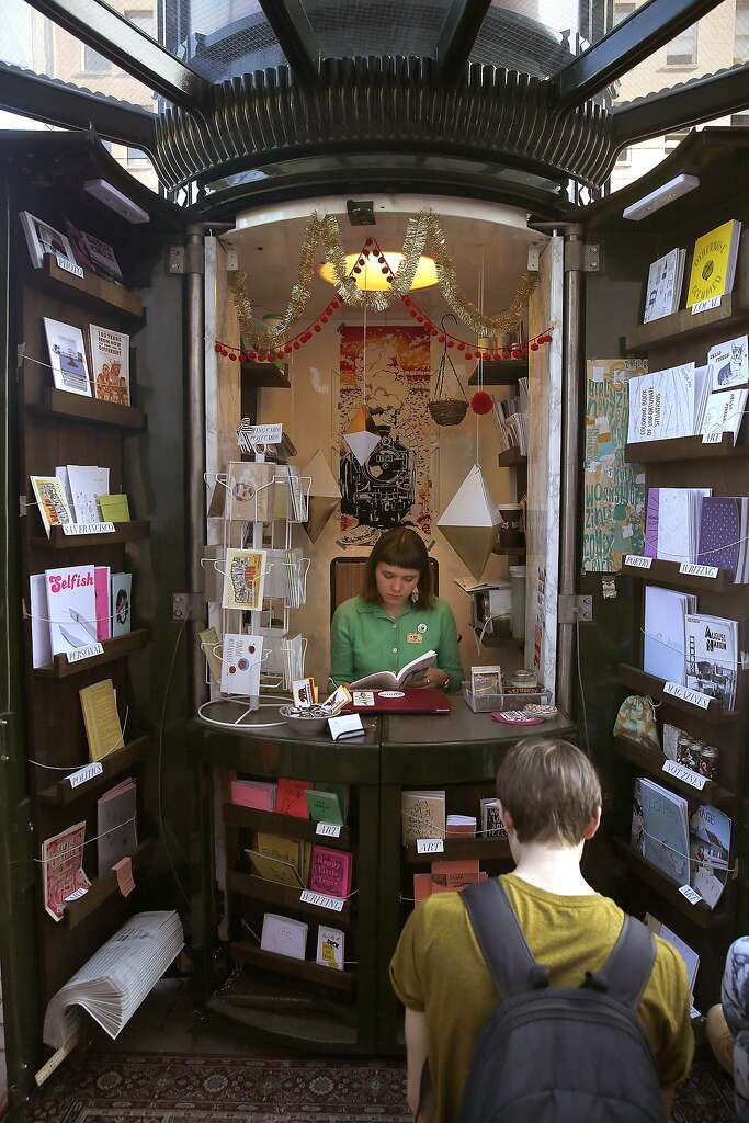 Zine Assistant Mae Powell In Newsstand Shows The Literature To Customers At Grand