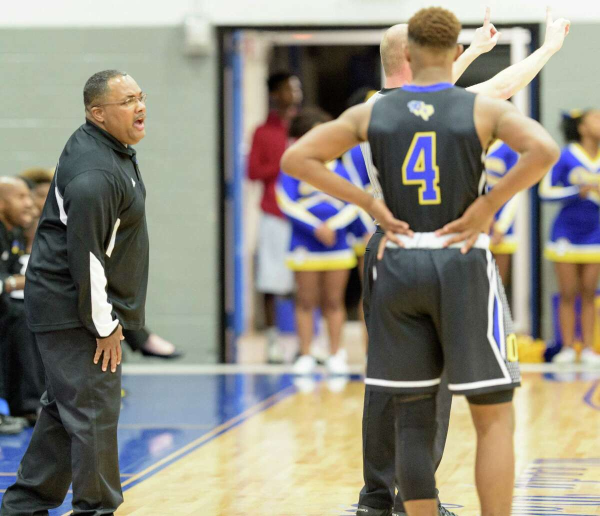 Beaumont Ozen Panthers Head Coach, Marquis Saveat shouts instructions to Travon Gipson (4) during a free throw in the second half against the Fort Bend Bush Broncos in a high school basketball game on Friday, February 26, 2016 at the Winnie Brown Gym at Sterling High School in Baytown Texas.