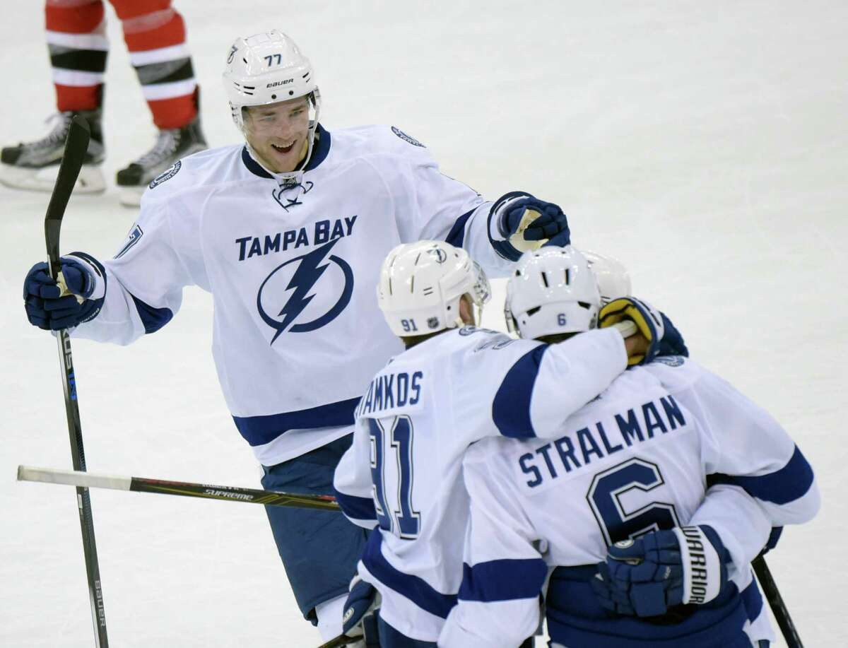 Tampa Bay Lightning's Victor Hedman (77), of Sweden, joins Anton Stralman, of Sweden, and Steven Stamkos to celebrate after Stamkos scored a goal during the second period of an NHL hockey game against the New Jersey Devils on Friday, Feb. 26, 2016, in Newark, N.J. (AP Photo/Bill Kostroun) ORG XMIT: NJBK105