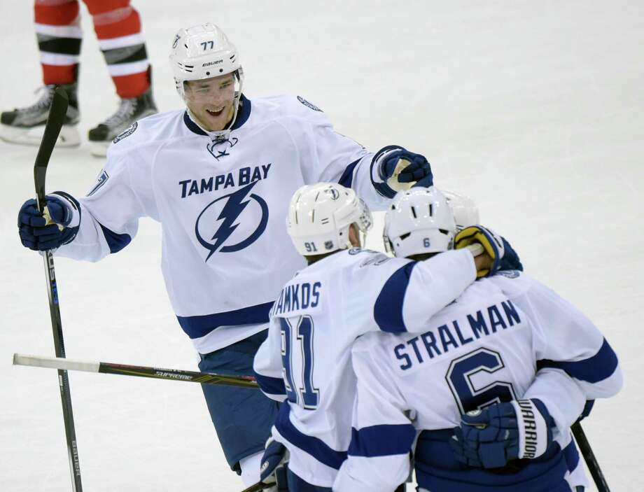 Tampa Bay Lightning's Victor Hedman (77), of Sweden, joins Anton Stralman, of Sweden, and Steven Stamkos to celebrate after Stamkos scored a goal during the second period of an NHL hockey game against the New Jersey Devils on Friday, Feb. 26, 2016, in Newark, N.J. (AP Photo/Bill Kostroun) ORG XMIT: NJBK105 Photo: Bill Kostroun / FR51951 AP