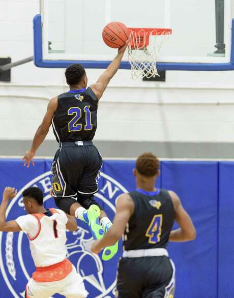 Beaumont Ozen's John Comeaux (21) soars to the basket for a layup in the first half of Friday night's Class 5A Region III playoff game against Bush at Baytown Sterling. Photo: Wilf Thorne / © 2016 Houston Chronicle