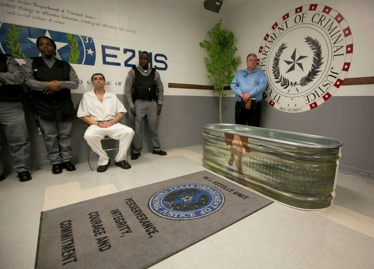 Inmate Ryan Castro, seated, waits to be baptized prison minister and volunteer chaplain at the TDCJ Estelle Unit in Hunstville, Texas on February 26th, 2016.