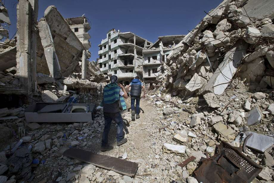 Syrian youths walk through the rubble of buildings in the city of Homs. The cease-fire went into effect at midnight Friday. Photo: Hassan Ammar, Associated Press