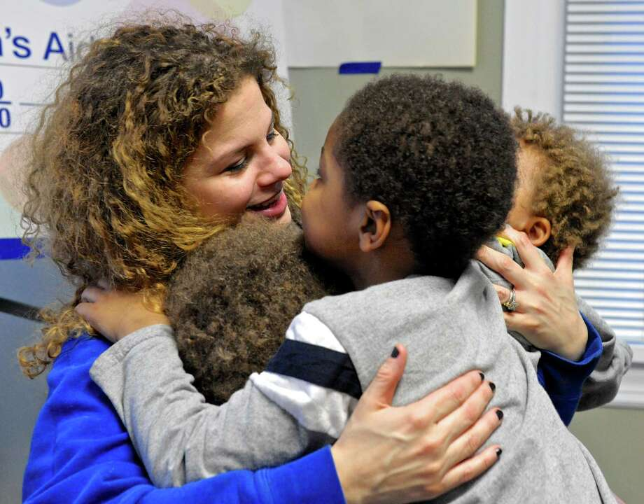 Katie gets a hug from her three sons. Their family could benefit from the governor's proposal to expand state-funded childcare subsidies to homeless children. Thursday, February 25, 2016, in Danbury, Conn. Photo: H John Voorhees III / Hearst Connecticut Media / The News-Times