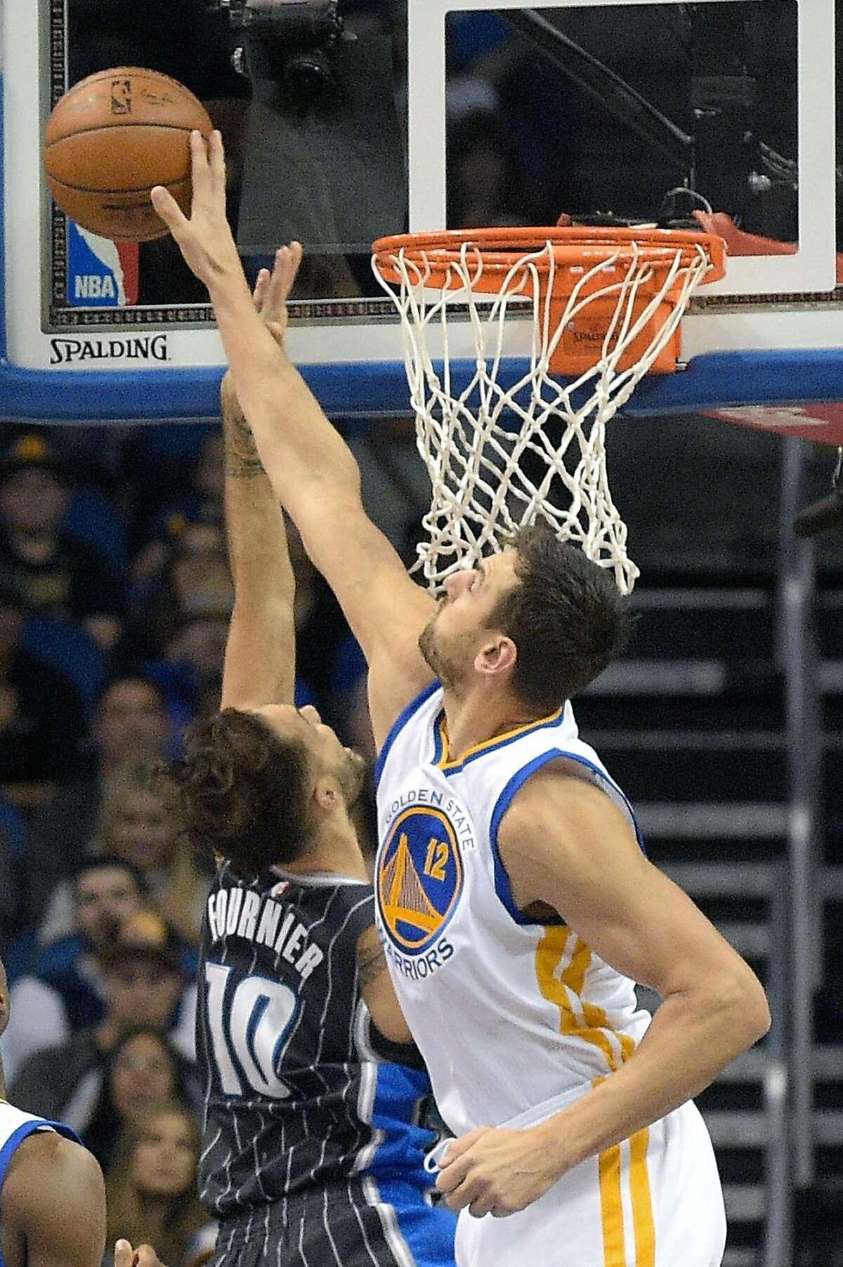 Warriors center Andrew Bogut (12) blocks a shot by Magic guard Evan Fournier (10) during Thursday's game in Orlando.