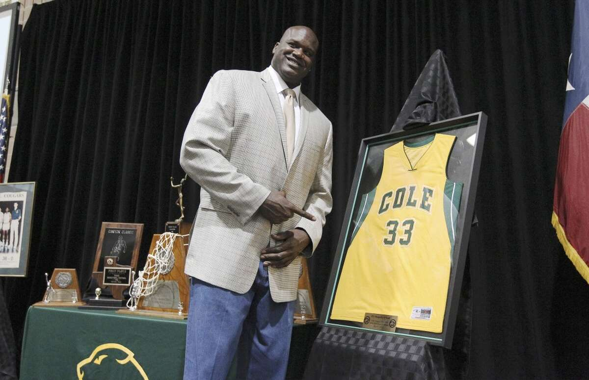 Shaquille O'Neal, Cole High School Retired basketball star Shaquille O'Neal poses with a jersey representing his school and number during his high school jersey retirement ceremony at Cole High School on Friday, mar. 7, 2014. O'Neal graduated from Cole in 1989 and took the basketball team to a 3A State championship. The school honored O'Neal by retiring his jersey with an accompaniment of guests including his former coaches and teammates from Cole High. (Kin Man Hui/San Antonio Express-News)