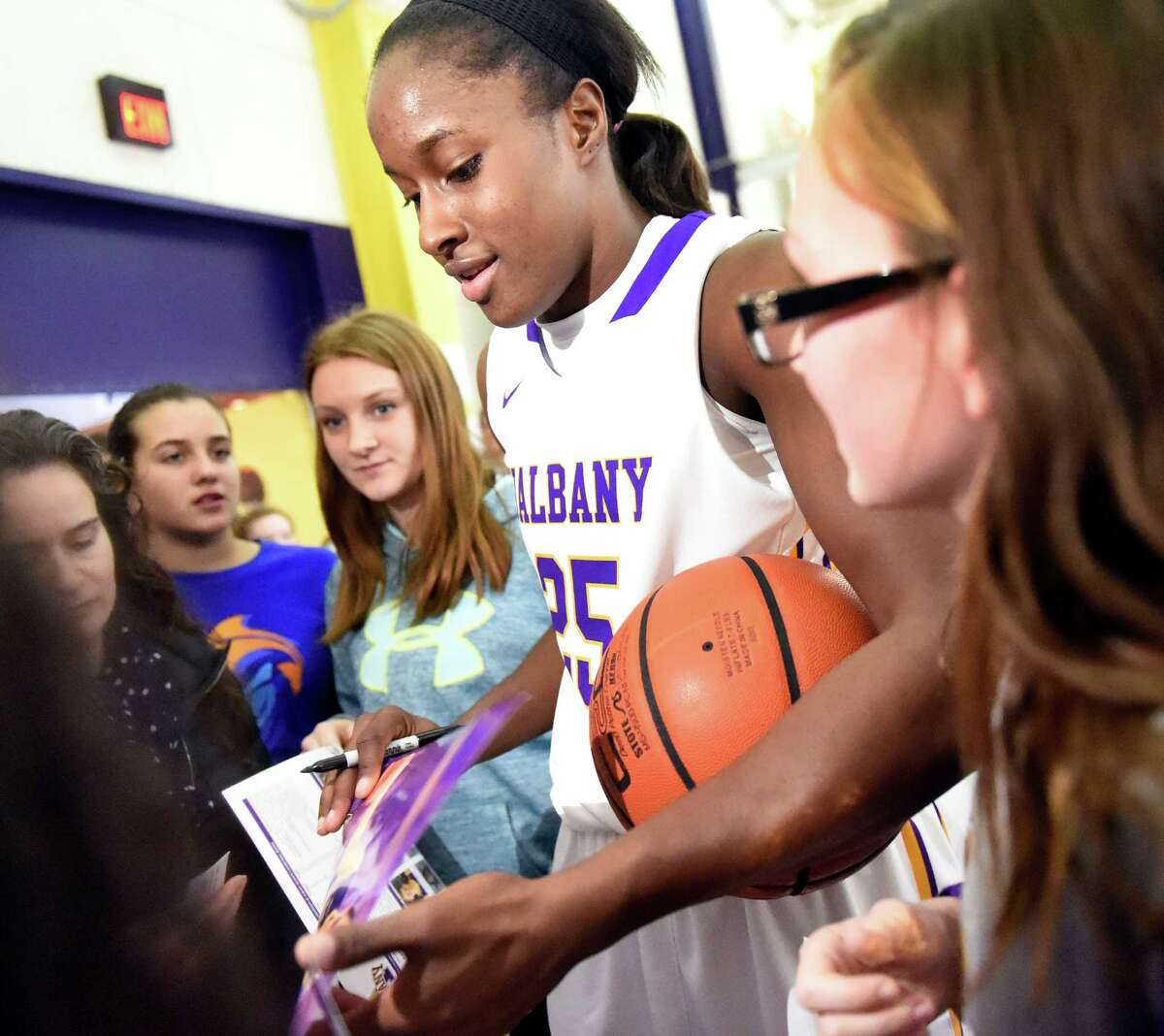 UAlbany's Shereesha Richards, center, signs autographs after reaching 2,000 career points in their basketball game against Vermont on Saturday, Jan. 9, 2016, at SEFCU Arena in Albany, N.Y. UAlbany won 77-42. (Cindy Schultz / Times Union)