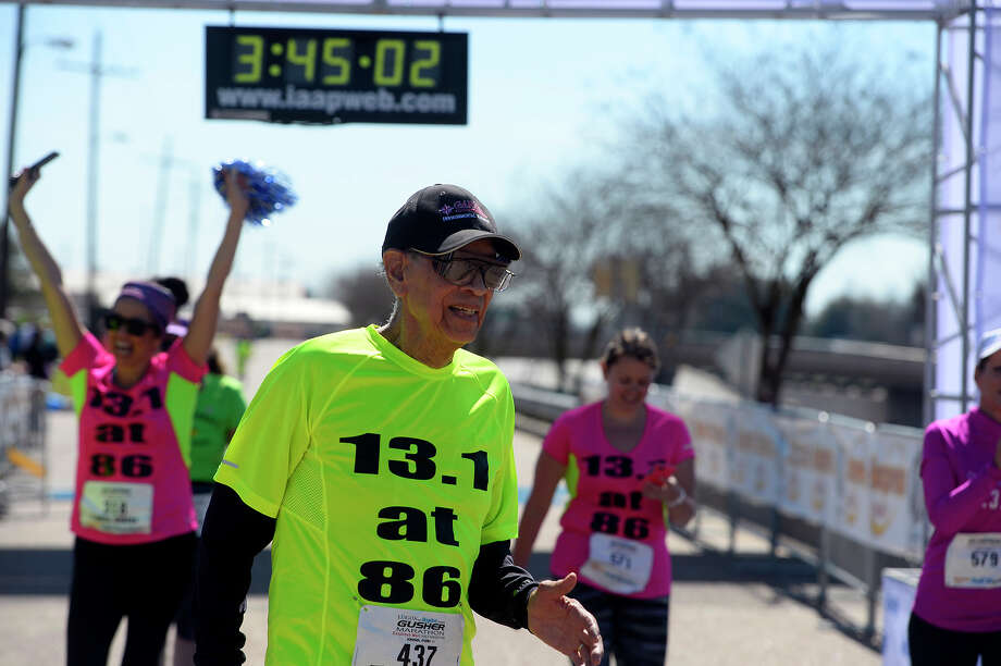 Jim Solis, 86, crosses the finish line of the Gusher half marathon on Saturday morning. Photo taken Saturday 2/27/16 Ryan Pelham/The Enterprise Photo: Ryan Pelham / ©2016 The Beaumont Enterprise/Ryan Pelham