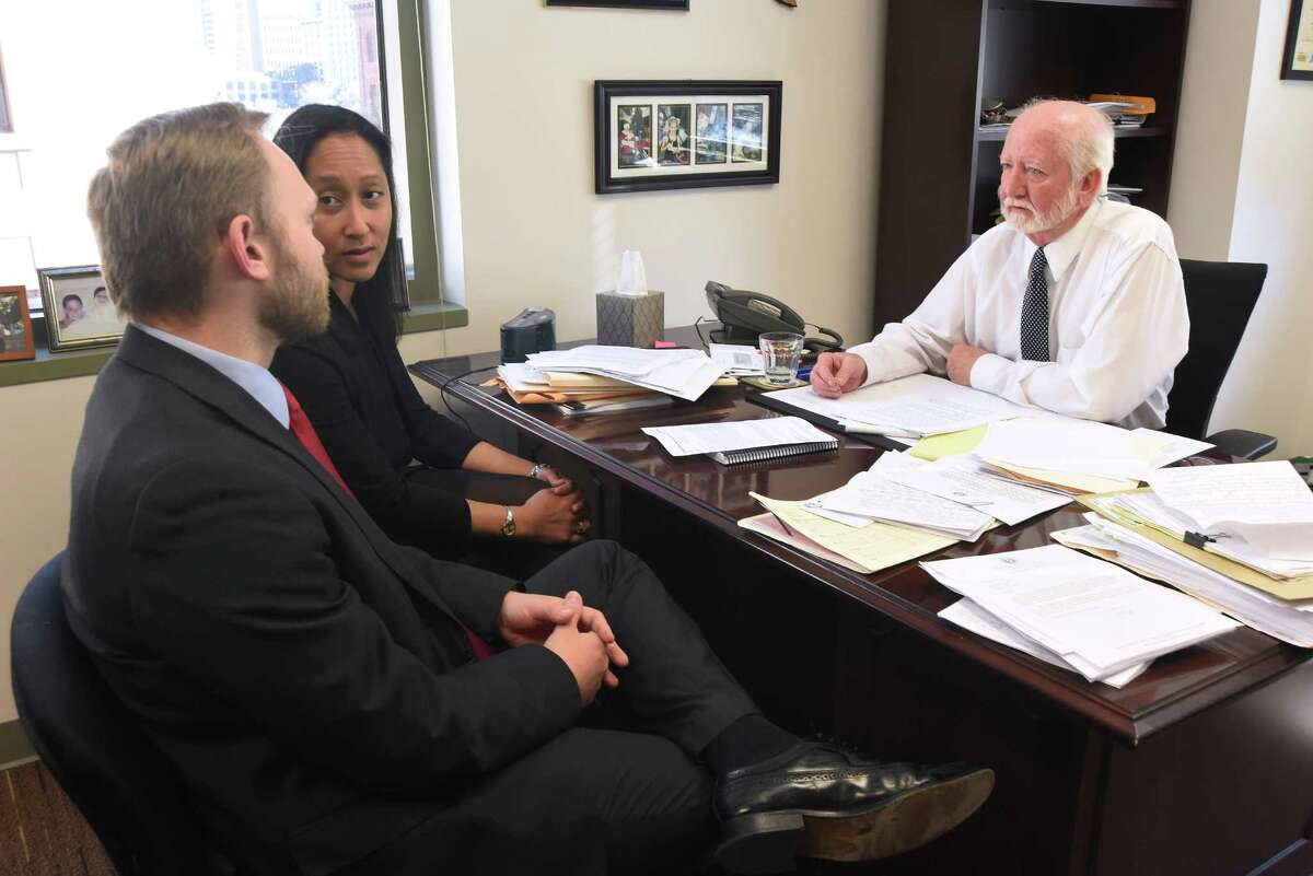 Jay Brandon, right, chief of the DA's Conviction Integrity Unit, speaks with his staff, Omiga Cape, middle, and Matthew Howard, left, on Tuesday, Feb. 16, 2016.