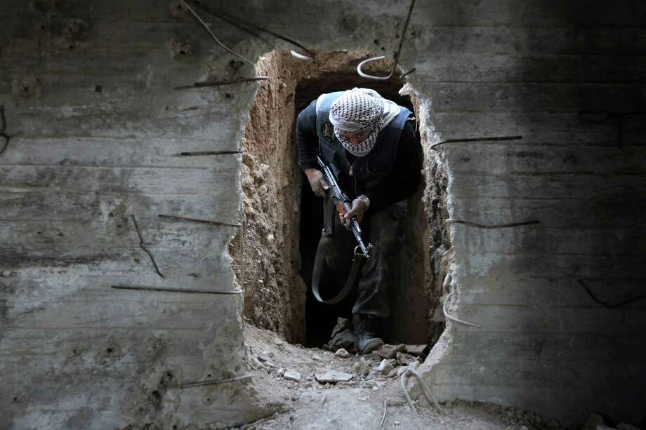 A Syrian rebel fighter comes out of a hiding position on the front line against government forces Friday in a town on the outskirts of Damascus, hours before a cease-fire began. Photo: AMER ALMOHIBANY, Stringer / AFP or licensors