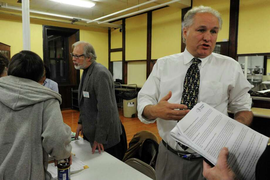 "Lloyd Wilson, right, who works for the state's Center for Environmental Health, handed out ""fact sheets"" at a Dec. 2 public meeting in Hoosick Falls. Two weeks later, after widening criticism of the state's handling of the case, the unit revised its position on the potential dangers of a toxic chemical found in the village's public water supply. (Michael P. Farrell/Times Union)"