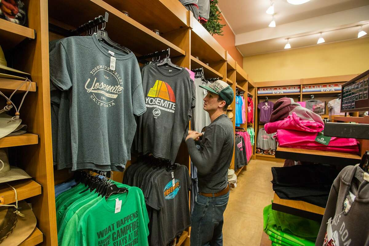 """A customer shops for t-shirts at the Village Store at Yosemite National Park on Friday, February 26, 2016 in Yosemite, CA. The new concessionaire for Yosemite National Park is Aramark which won a bid for the 15 year contact over current contractor Delaware North. Delaware North is claiming intellectual property rights which it purchased in 1993 for the names of several hotels, Curry Village, Badger Pass Ski Area area and the name, """"Yosemite National Parks."""" Signage will have to be changed or covered when Aramark takes over. The National Park Service and Aramark have decided to rename the contested properties rather than pay the requested $50 million by Delaware North."""
