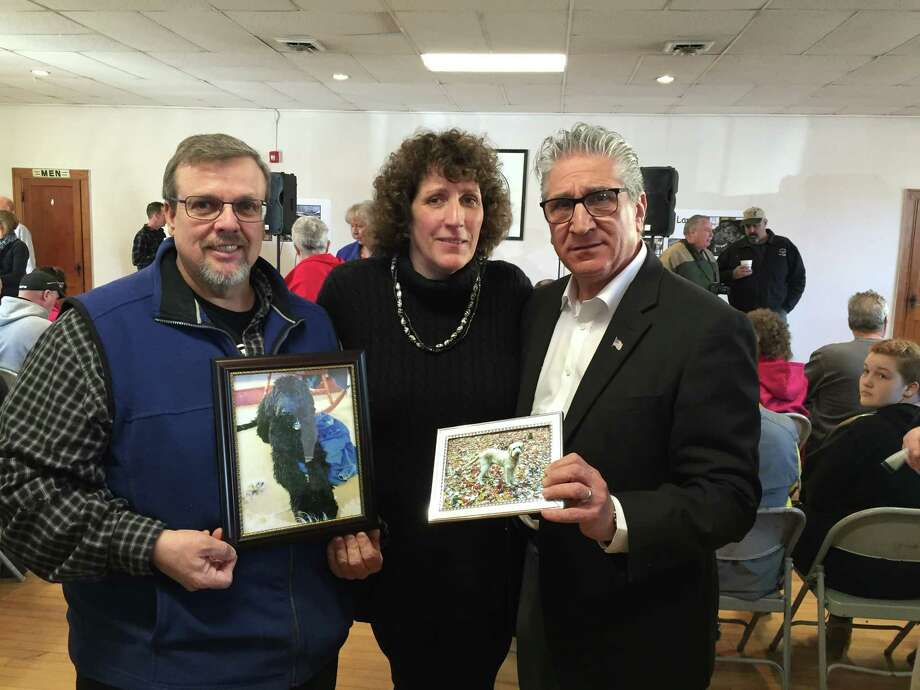 Pat and Denise Krohn, left and center, and Assemblyman Jim Tedisco holding up photos of Kirby and Quigley at a rally Saturday, Feb. 28, 2016, at Florida Town Hall. Montgomergy County, N.Y. to push for passage of a law that would make it a felony offence to harm an animal while committing another felony crime in New York state. (Adam Kramer)