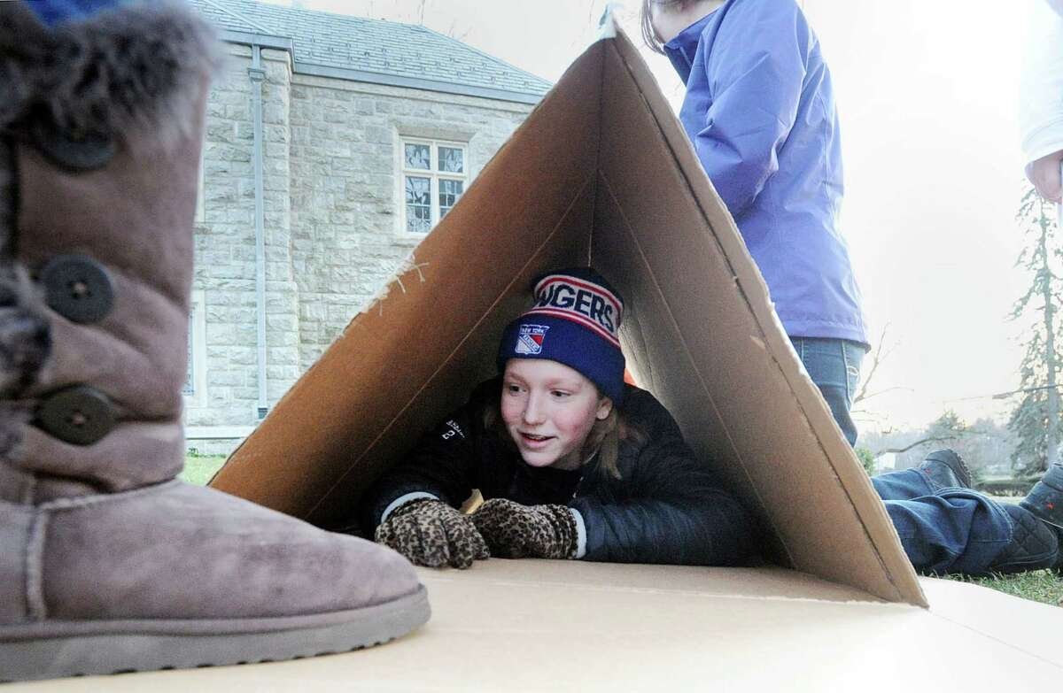 Greenwich High School sophomore Jessie Aselin, 15, tests out the shelter she constructed that was part of project of the Youth Groups of First Congregational Church, who were attempting to gain a firsthand knowledge of the homeless experience, built a homeless encampment made out of cardboard boxes on the front lawn of the First Congregational Church, Old Greenwich, Conn., Saturday night, Feb. 27, 2016. Donald Haviland, a youth group minister at the church said the group would be spending the night in the shelters they contructed to raise awareness about homelessness and to seek donations of goods for Inspirica, a homeless shelter in Stamford.