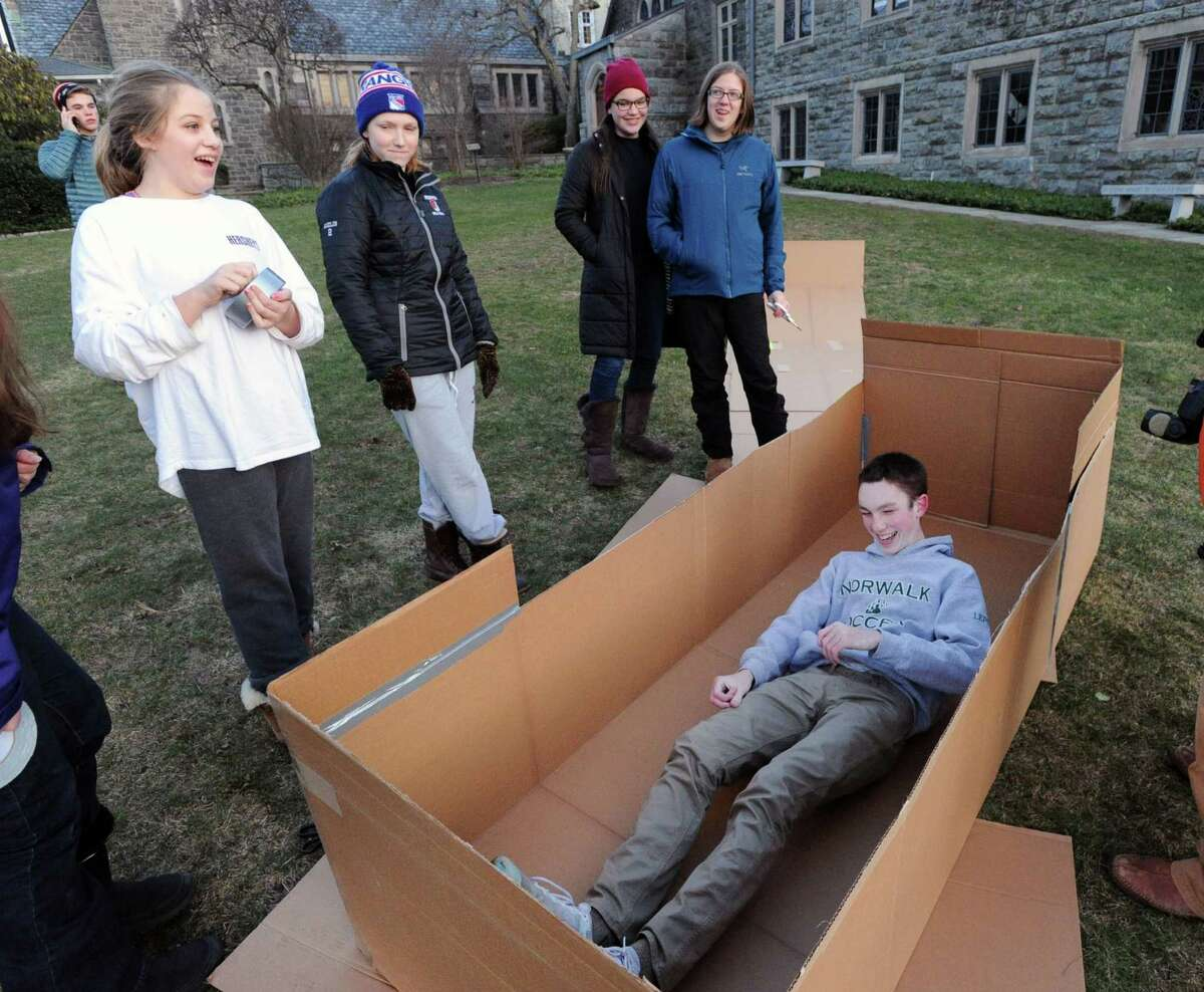 At right, Daniel Lepoutre, 16, of Norwalk, tests out his homeless shelter as part of the project by the Youth Groups of First Congregational Church, in an attempt to gain firsthand knowledge of the homeless experience, built a homeless encampment made out of cardboard boxes on the front lawn of the First Congregational Church, Old Greenwich, Conn., Saturday night, Feb. 27, 2016. Donald Haviland, a youth group minister at the church said the group would be spending the night in the shelters they contructed to raise awareness about homelessness and to seek donations of goods for Inspirica, a homeless shelter in Stamford.