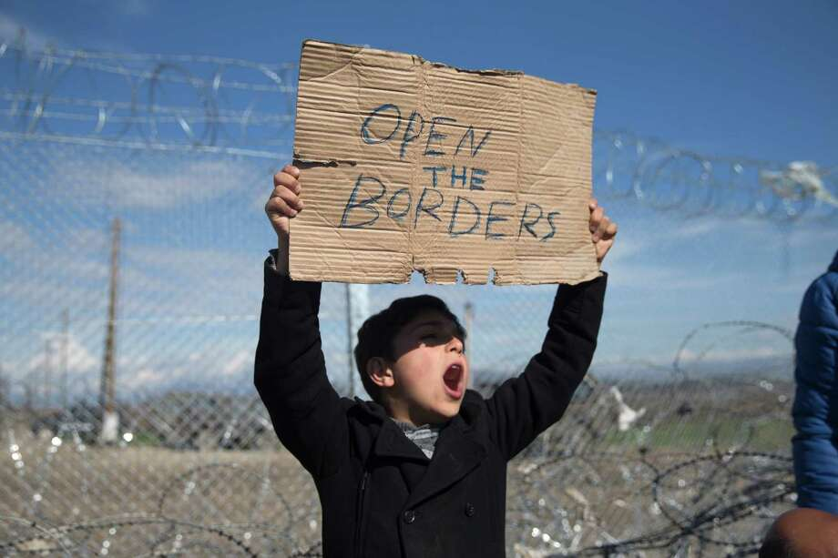 A boy shouts during a protest Saturday by refugees and migrants in front of the wire fence that separates Greece from Macedonia at the border station of Idomeni. Photo: Petros Giannakouris, STF / AP