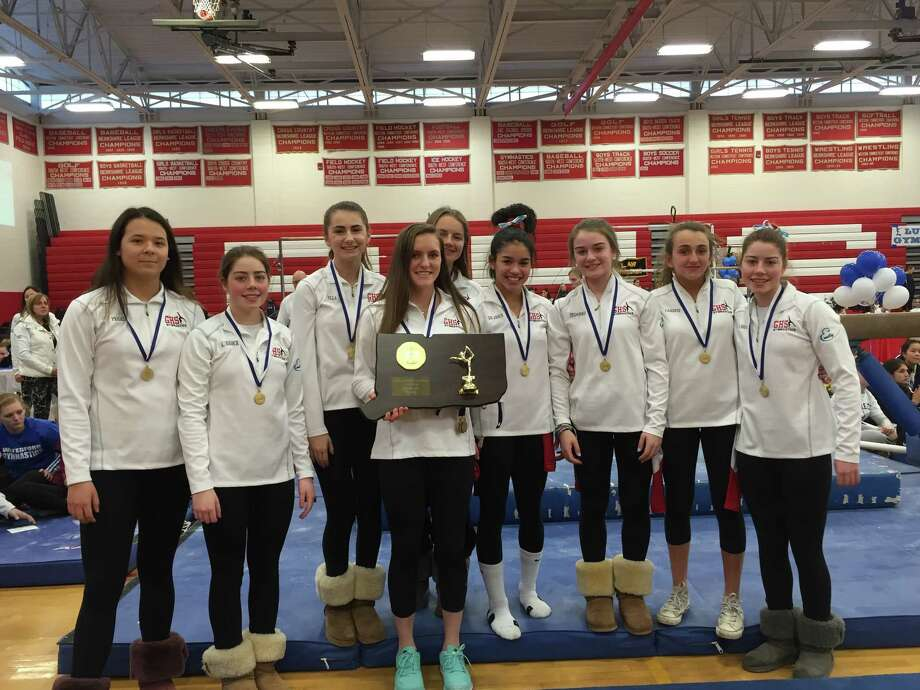 Greenwich High School senior gymnastics captain Jessica Freiheit, center, holds the championship plaque while surrounded by her teammates after the Cardinals won the Class L championship at Pomperaug High School on Saturday Photo: Contributed Photo /Contributed Photo