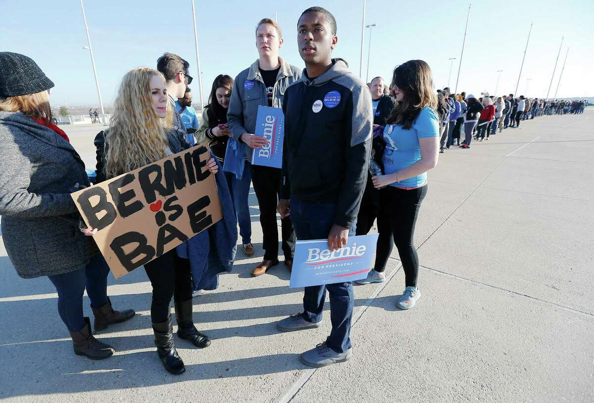 Elijah Miller (front right) and Erin Ckodre (second from left) join others from the Texas State University's College Democrat organization as they wait in line to see Democratic presidential candidate and U.S. Senator Bernie Sanders at a rally at the Circuit of the Americas near Austin on Saturday, Feb. 27, 2016 as the campaign stumps for the upcoming Texas Primary. Thousands of supporters lined up to see Sanders and to hear his proposals if he were to be elected president. Sanders touched on topics of workers' wages, immigration, health insurance, bank reform and free public college and university tuition. Over 6,500 were reported to be at the rally as many were still filing in as Sanders spoke. The Texas Primary will take place on March 1. (Kin Man Hui/San Antonio Express-News)