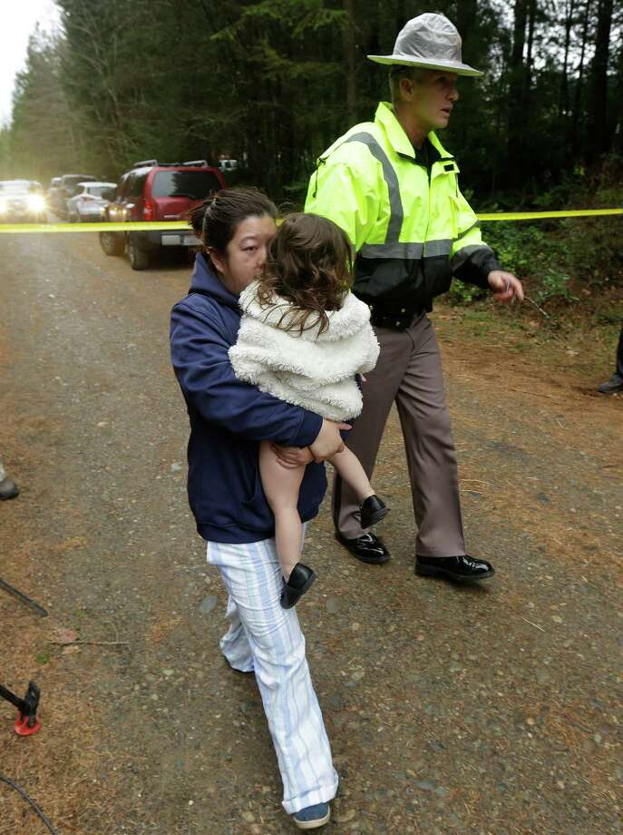 Mason County Sheriff's Chief Criminal Deputy Ryan Spurling, right, escorts Adeline Peebles, left, and a child away from the scene of a fatal shooting Friday, Feb. 26, 2016, near Belfair, Wash. Peebles said she was a friend of the people involved in the shooting. (AP Photo/Ted S. Warren) Photo: Ted S. Warren, STF