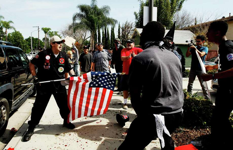 "A Ku Klux Klansman fends off angry counter-protesters Saturday after KKK members started a ""White Lives Matter"" rally at Pearson Park in Anaheim, Calif. Photo: Luis Sinco, MBR / Los Angeles Times"