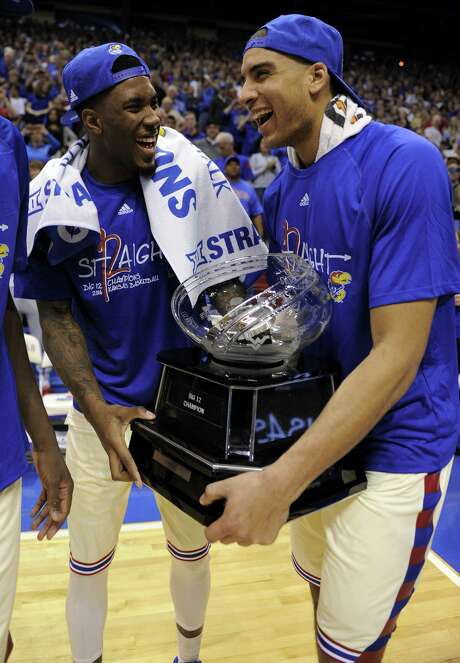 Jamari Traylor, left, and Landen Lucas prepare to do the heavy lifting as Kansas celebrates clinching a share of its 12th consecutive Big 12 regular-season title. Photo: Ed Zurga, Stringer / 2016 Getty Images