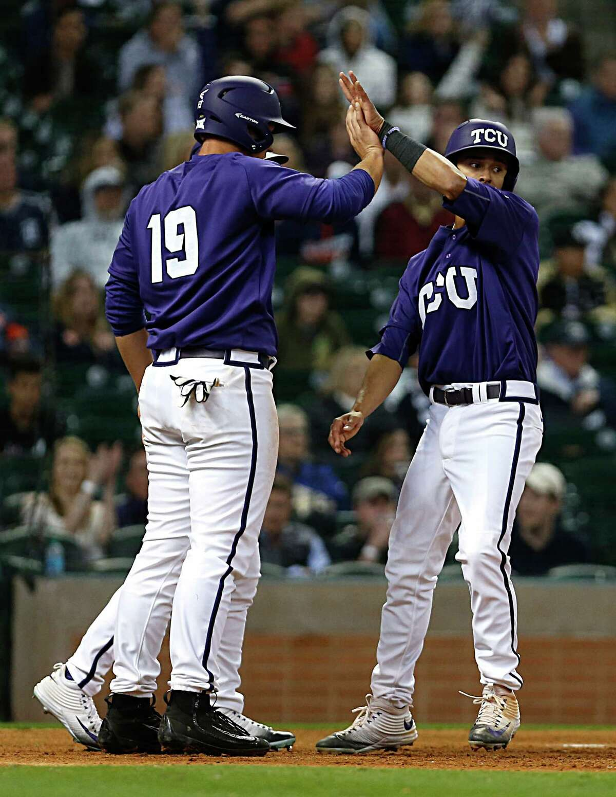 TCU pitcher Luken Baker left, high fives teammate Elliott Barzilli right, after the pair scored on a 2 run double by TCU outfielder Dane Steinhagen during second inning of the 2016 Shriners Hospitals for Children College Classic baseball game at Minute Maid Park Saturday, Feb. 27, 2016, in Houston.