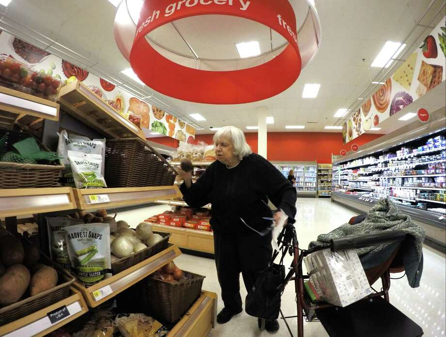 Carlton picks groceries at Target, which offer a variety of food items and limited fresh fruits and vegetables. Photo: Matthew Brown / Hearst Connecticut Media / Stamford Advocate