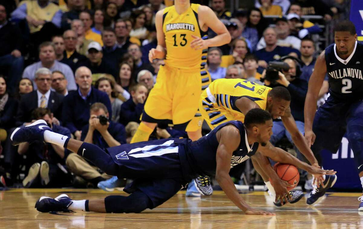 Villanova forward Darryl Reynolds, front, dives for the loose ball against Marquette guard Traci Carter, back, during the second half of an NCAA college basketball game Saturday, Feb. 27, 2016, in Milwaukee. Villanova defeated Marquette 89-79. (AP Photo/Darren Hauck) ORG XMIT: WIDH112