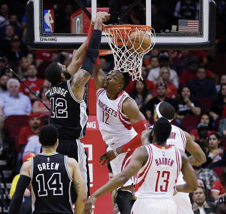 San Antonio Spurs forward LaMarcus Aldridge (12) dunks on Houston Rockets center Dwight Howard (12) as guard Danny Green (14), guard James Harden (13) and center Josh Smith (5) watch during the first half of an NBA basketball game Saturday, Feb. 27, 2016, in Houston. (AP Photo/Bob Levey) Photo: Bob Levey, FRE / Associated Press / FR156786 AP