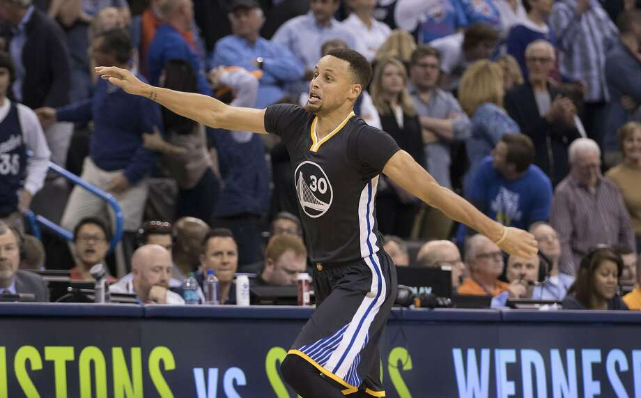 After scoring the winning three-point shot on Saturday night, Stephen Curry uses his arms to demonstrate to the Oklahoma City Thunder crowd how deep his range is. On Tuesday, the NBA changed the official distance of the shot from 32 feet to the much better 37. Photo: J Pat Carter, Getty Images