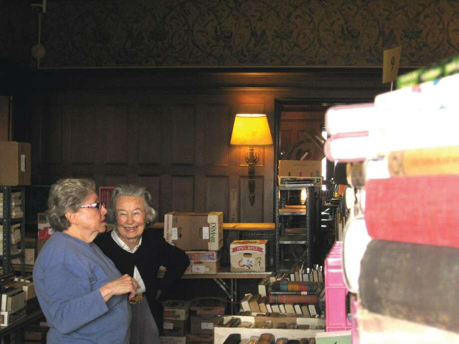 Eddy Sherwood and Babs White stock shelves at Waveny House with hundreds of books on Tuesday in preparation for the 50th and final Smith College book sale. Photo: Brittany Lyte / New Canaan News